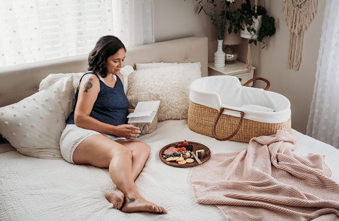 woman laying on bed reading a book and drinking a glass of water. Plate of food and bassinet nearby